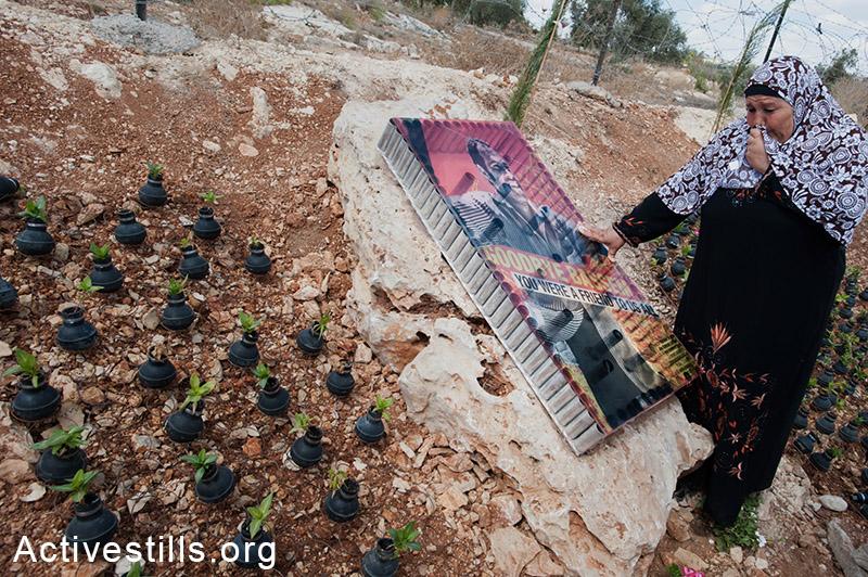 אמו של באסם אבו-רחמה, סובייה, בוכה באתר ההנצחה לבנה במהלך אירוע המציין 8 שנים למאבק נגד הכיבוש בכפר בילעין, הגדה המערבית, 2013. ריאן רודריק ביילר / אקטיבסטילס