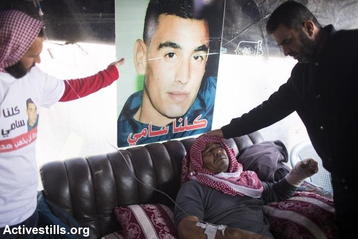 ח'אלד אל-ג׳עאר יושב בסוכת האבלים לאחר ששוחר מהמעצר והוכה (צילום: אקטביסטילס)