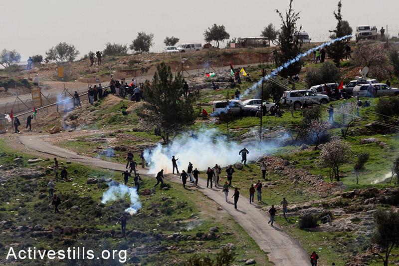 פעילים רצים מגז מדמיע שנורה עליהם על ידי חיילים, במהלך הפגנה בבלעין, הגדה המערבית, 2008. טס שפלן / אקטיבסטילס