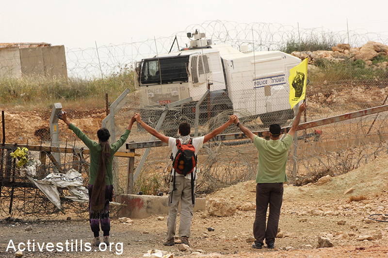 פעילים בינלאומיים מרימים ידיים כסימן להפגנה לא-אלימה במהלך הפגנה בבילעין, הגדה המערבית, 2012. אחמד אל-באז / אקטיבסטילס