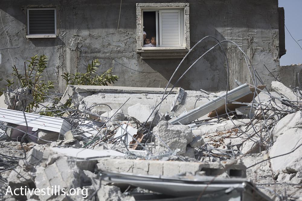 שכנים מביטים על ביתה של הנא אל-נאקיב, לוד (אורן זיו / אקטיבסטילס)