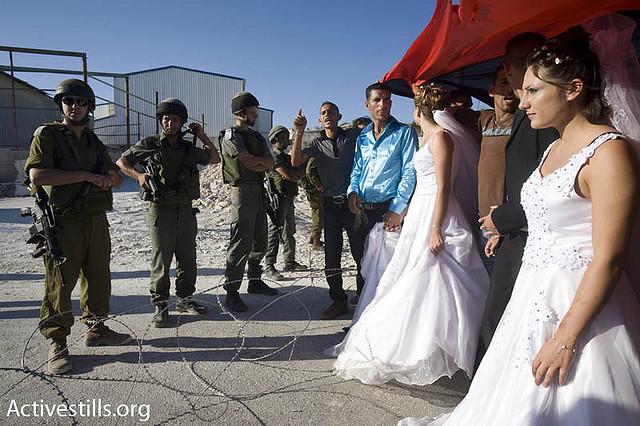 פלסטינים מקיימים מייצג חתונה במהלך הפגנה לא אלימה בגדה המערבית. המפגינים ממחו על המגבלות שמטילה ישראל על תנועה שפוגעת גם בזכותלהתחתן ולהקים משפחה. (אורן זיו/אקטיבסטילס)
