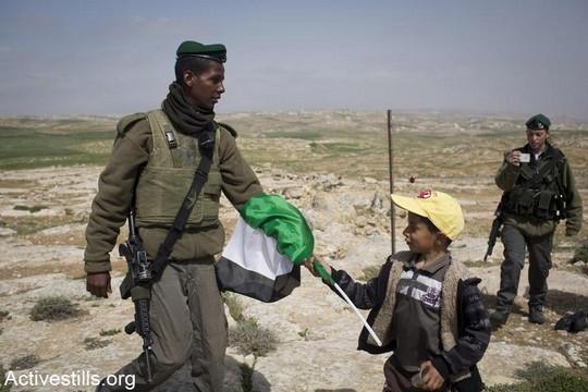 חייל מנסה לחטוף מילד דגל פלסטין. דרום הר חברון, מרץ 2013. (אורן זיו/אקטיבסטילס)