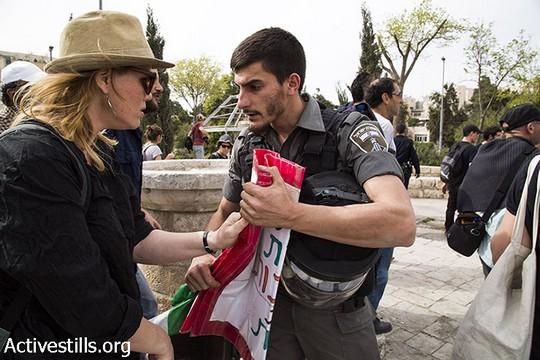 שוטרים קורעים שלטים בהם אחזו מפגיני שמאל בהפגנה נגד פינוי משפחות מבתיהן בירושלים המזרחית (מרייקה לאוקן וקרן מנור/אקטיבסטילס)