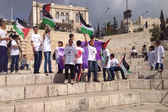 ילדי שכונות סילוואן ועיסאוויה מפגינים במסלול של מרתון ירושלים. המרתון שעבר בשטחי העיר שמעבר לקו התפר גרם לחסימה של שכונות רבות במזרח העיר.