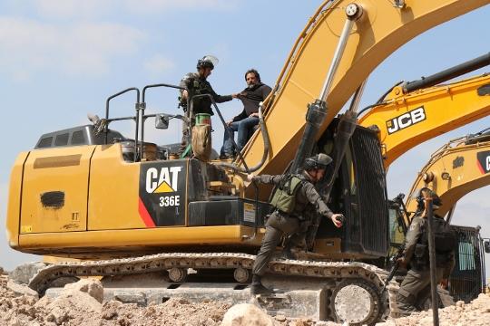 מפגין יושב על בולדוזר ועוצר עבודות בנייה באבו דיס (אחמד אל-באז / אקטיבסטילס)