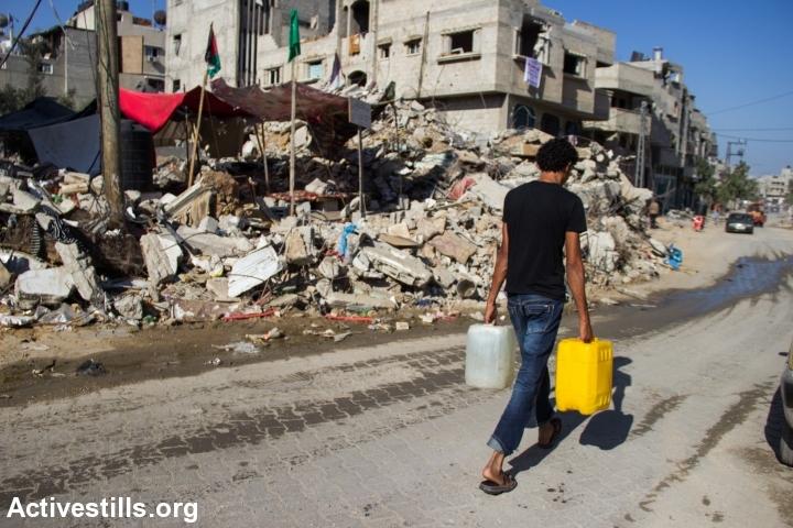 תושב שכונת שג'אעיה סוחב מיכלי מים, ספטמבר 2014 (באסל יאזורי / אקטיבסטילס)