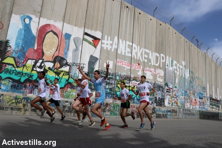 רצים לצד חומת ההפרדה בבית לחם. מרתון 2015. (אחמד אל-באז/אקטיבסטילס)