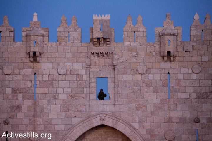 """שוטר מג""""ב עומד על המשמר מעל שער שכם בירושלים המזרחית. לעיתים קרובות מתקיימות באזור זה הפגנות ועימותים בין פלסטינים תושבי מזרח ירושלים למשטרה. (אקטיבסטילס)"""