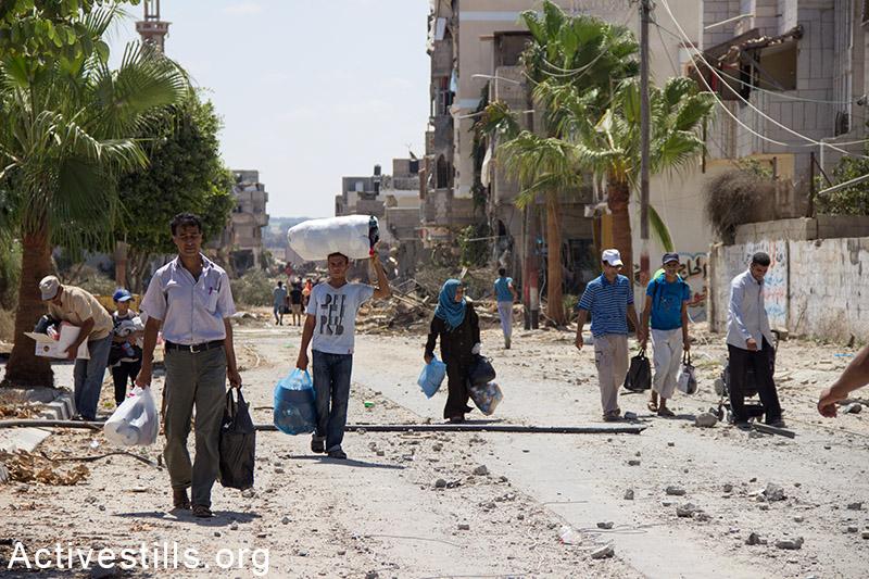 אנשים בורחים עם מטלטליהם, ח׳וזעה, רצועת עזה, 3 אוגוסט, 2014. באסל יאזורי / אקטיבסטילס
