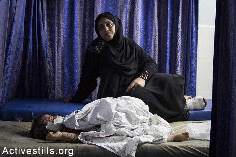 אישה מחכה לטיפול בילדה הפצוע לאחר הפגזה ישראלית, בבית החולים אל-שיפא, עזה, 30 יולי, 2014. באסל יאזורי / אקטיבסטילס