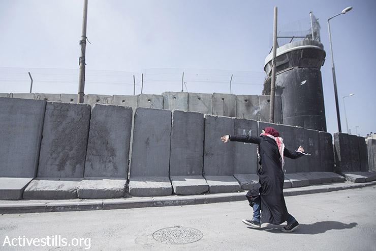 אישה פלסטינית מיידה אבנים בהפגנת יום האישה הבינ״ל סמוך למחסום קלנדיה, 7 במרץ, 2015. (אקטיבסטילס)