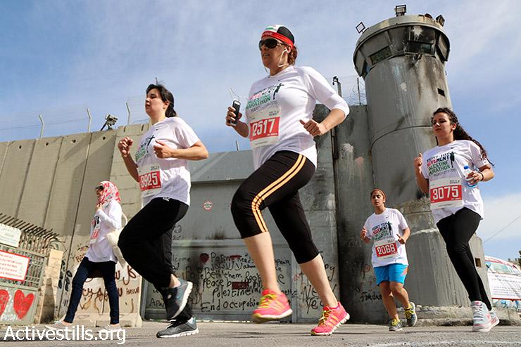 משתתפות במרתון הפלסטיני השלישי רצות סמוך לחומת ההפרדה בבית לחם, 27 במרץ, 2015. כ-3200 פלסטינים ובינ״ל השתתפו במרתון השנתי, תחת הכותרת- הזכות לחופש תנועה. (אקטיבסטילס)