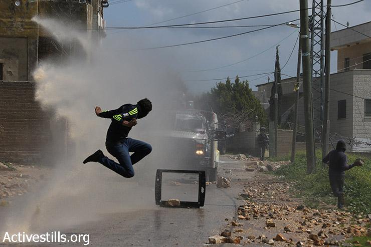 צעיר פלסטיני קופץ באויר בזמן שתותח מים צבאי יורה עליו מים, במהלך ההפגנה השבועית נגד הכיבוש בכפר קאדום, 13 במרץ, 2015. (אקטיבסטילס)