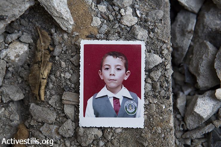 תמונה של עבדאללה עבדל חאדי אל מג'דלאווי מונחת בין הריסות ביתו בג'בליה, עזה, 19 במרץ 2015. עבדאללה (13) נהרג בהפצצה שהתרחשה ללא כל התראה מוקדמת ב3 באוגוסט 2014. יחד איתו נהרגו אחיו עבדל רזאק (19) ושני בני דודיו ראוון (9) ומחמוד (8). (אקטיבסטילס)