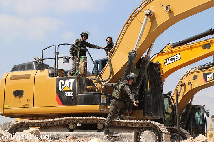 חיילים עוצרים פעיל ישראלי במהלך פעולה ישירה לעצירת הפקעת אדמות באזור E1, סמוך לאל-עזרייה, 17 במרץ, 2015. מעל 15,000 פלסטינים גרים באזור E1 ונמצרים תחת סכנת פינוי והפקעת קרקעות.  (אקטיבסטילס)