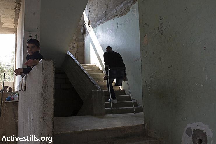 וואהל אל-נמלה, 26, עולה במדרגות ביתו ברפיח, עזה, 18 במרץ, 2015. בני משפחת אל-נמלה ברחו מביתם בזמן ההתקפה הישראלית בקיץ 2014 ונפגעו ע״י טילים ישראלים כ-600 מטר מביתם. שלושה מבני המשפחה נהרגו- אחיו של וואהל, יוסף ואישתו וואלה, ואחותו בת ה-11, אנגם. וואהל נפצע אף הוא בהפצצה, אישתו איבדה את 2 רגליה ובנם בן ה-3 איבד אף הוא חלק מרגלו השמאלית. (אקטיבסטילס)