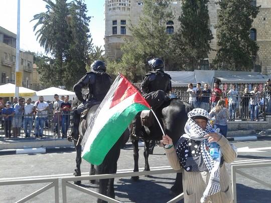 קשישה פלסטינית שהקפידה להיצמד לשוטרים עם דגל פלסטין קטן ביד (אורלי נוי)