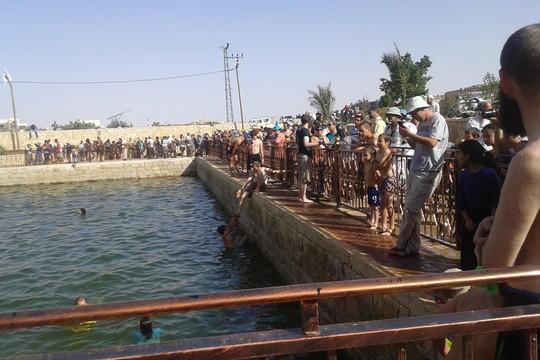 מאות המתנחלים נכנסו למים בעוד הפלסטינים אולצו להישאר בחוץ. בירכת אל-כרמל (צילום: נסר נוואג'עה, בצלם)