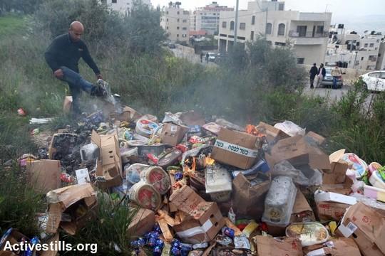 פעילים פלסטינים משמידים מוצרים של חברות ישראליות במהלך קמפיין חרם על חברות מזון ישראליות (אחמד אל-באז/אקטיבסטילס)