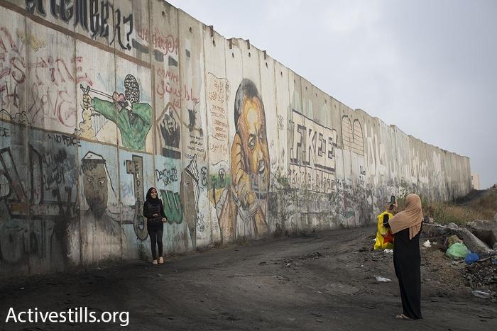 נשים מצטלמות ליד חומת ההפרדה, קלנדיה (אורן זיו / אקטיבסטילס)