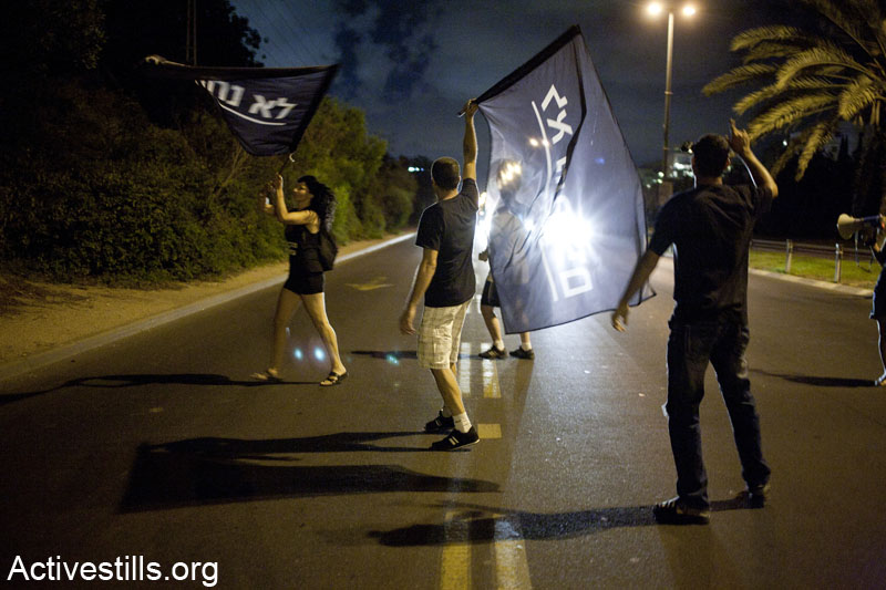 פעילות מקבוצת הלא נחמדים/לא נחמדות חוסמות את איילון במהלך הפגנה מול ביתו של שר האוצר דאז, יאיר לפיד, בתל אביב. 15 ביוני 2013. (קרן מנור/ אקטיבסטילס)