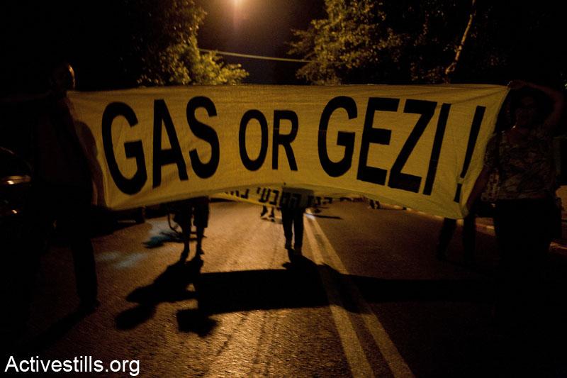 מפגינות חוסמות כביש בתל אביב במהלך הפגנה נגד הפרטת הגז. על הבאנר הכיתוב: ״גז או גזי״ המתייחס למאבק הגז בישראל ולהפגנות ההמונים בתורכיה באותה תקופה. 19 ביוני 2013. (קרן מנור/ אקטיבסטילס)