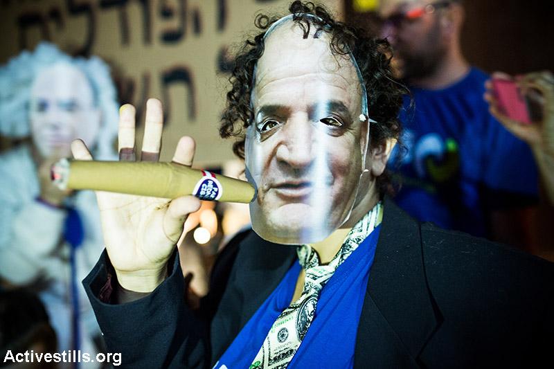 מפגין עוטה מסכה של יצחק תשובה במהלך מחאת הגז בתל אביב. 27 ביוני 2015. כ-4000 איש חסמו כבישים רבים לשעות ארוכות וכמה מפגינים נעצרו על ידי המשטרה. (יותם רונן/ אקטיבסטילס)