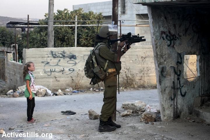 חייל מכוון נשק לעבר הפגנה, נבי סאלח, 2011 (אן פאק / אקטיבסטילס)