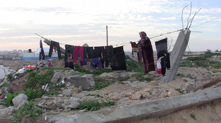 ופאא עוואג'ה תולה כביסה על הריסות מה שהיה פעם בית משפחתה, שנהרס במלחמת 2014 (צילום: ג'ן מרלו)