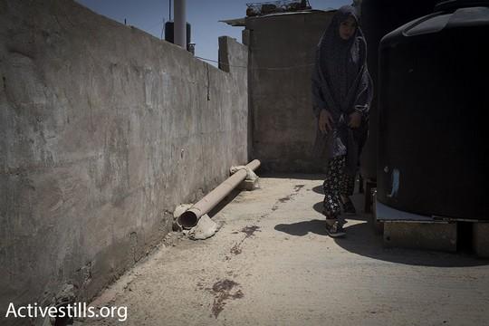 בת דודתו של אבו לטיפה מצביעה על עקבות וכתמי הדם שמובילים מגג השכנים בחזרה לבית משםחת אבו לטיפה. קלנדיה, 27 ביולי 2015. (אורן זיו/אקטיבסטילס)