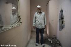 מג'יד אל-זים, בן 52, עומד בביתו ההרוס. בקיר הימני ניתן לראות חור שנגרם מפגיעת טיל ששוגר לעבר הבית ממזל״ט צבאי, ואשר גרם גם לפציעתו של אל-זים, עזה, 14 ביולי 2014. הטיל שוגר כאזהרה לפני תקיפה אווירית על על בית סמוך, נוהל הידוע גם בכינוי ״הקש בגג״. (אן פאק/אקטיבסטילס)