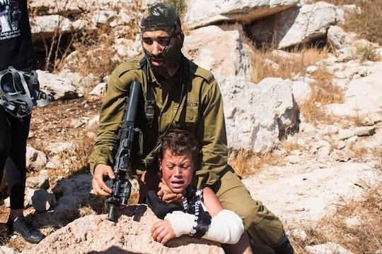 חייל תופס את מוחמד תמימי בן ה-12באלימות במהלך הפגנה בכפר נבי סלאח (צילום: כראם סלים)