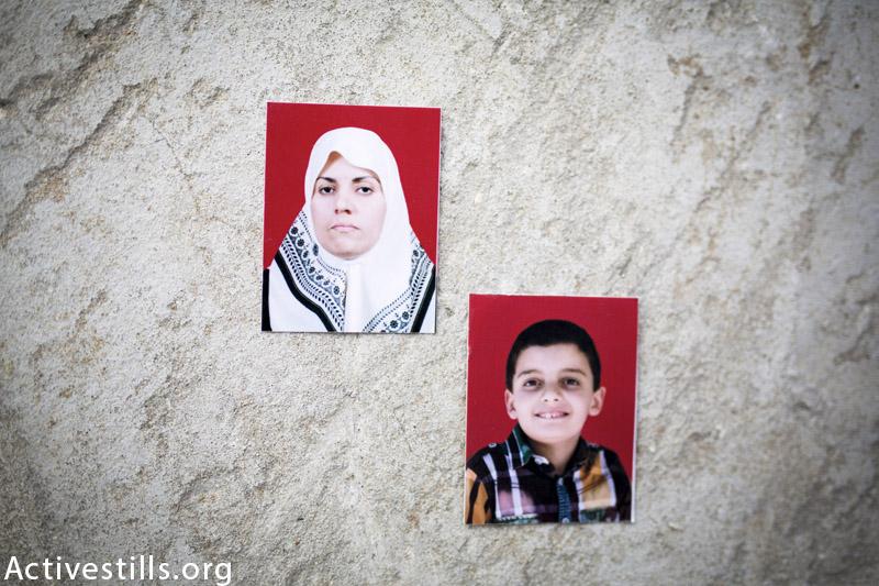 תמונות של ניסראן אחמד (38) ובנה (חוסיין חאלד אחמד (8), מצולמות על הריסות המשפחה בדיר אל-באלאה, 25 מרץ, 2015. (אן פאק / אקטיבטסילס)