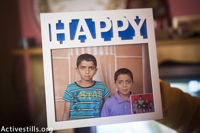 תמונה ממוסגרת של אחמד מוסטפא זו׳רוב (15) ואחיו מוחמד מוסטפא זו׳רוב (12) מצולמות בבית בראפח, בפברואר 10, 2015. השניים נהרגו במתקפה ישראלית ב 1 אוגוסט, 2014, בהפצצת בית דודם. 14 בני משפחה נוספים נהרגו בהפצצה. (אן פאק / אקטביסטילס)