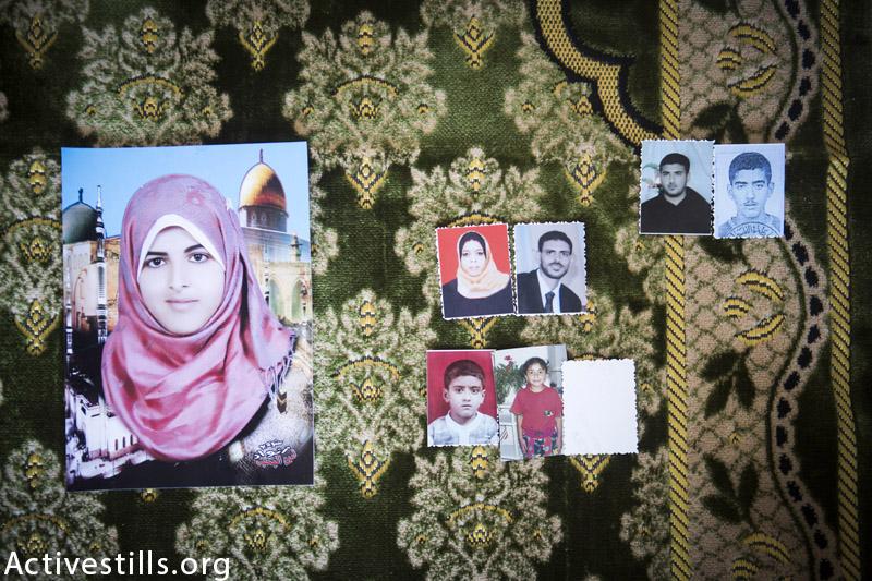 תמונות משפחת אל-לאו מצולמות על שטיח בבית המשפחה, דיר אל-באלה, עזה, ספטמבר 16, 2014. שמונה מחברי המשפחה נהרגו במתקפה ב 20 לאוגוסט 2014. (אן פאק / אקטיבסטילס)