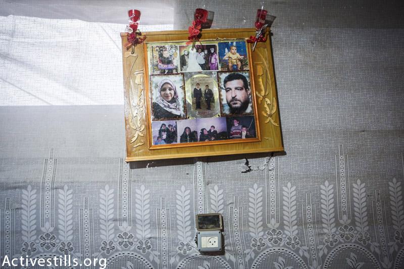 תמונות משפחתו של זאקי וואדאן, מצולמות באוהל זמני בבית ח׳אנון, עזה, פברואר 18, 2015. שמונה מחברי המשפחה, בעיקר נשים וילדים, נהרגו במתקפה על בית המשפחה ב 22 ליולי, 2014. (אן פאק / אקטיבסטילס)
