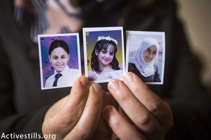 תמונות שלושה אחים (משמאל לימין): מוחמד (12), יארה (8) ונאדים (16) ממשפחת מחמוד אל-פארה, מצולמים בבית המשפחה בחאן יוניס, פברואר 22, 2015. תשעה מחברי המשפחה נהרגו בזמן שהלכו ברחוב בזמן בריחה מהתקפות ישראליות ב״יום שישי השחור״ בעזה, ה 1 לאוגוסט  2014. (אן פאק / אקטיבסטילס)