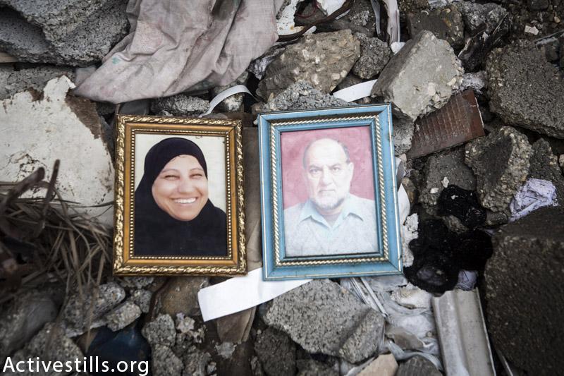 תמונות של הזוג, איברהים אבדואללה אבו-אטה (67) ואישתו ג׳מילה (55), מצולמות על חורבות ביתם במחנה הפליטים ג׳אבליה, רצועת עזה, פברואר 23, 2015. הם נהרגו בהתקפה ישראלית יחד עם שני ילדיהם ונכד ב 24 ליולי, 2014. (אן פאק / אקטיבסטילס)