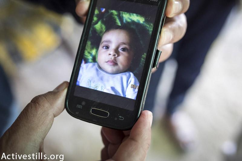 תמונה של אבדל האדי האייל אבו דאהרוג׳י (2) מוצגת על ידי קרוב בבית משפחת אבו-דאהרוג׳י, אל-זאווידאה, עזה, 17 מרץ, 2015. התינוק נהרג יחד עם כל משפחתו הקרובה, הוריו ואחיו. (אן פאק / אקטיבסטילס)
