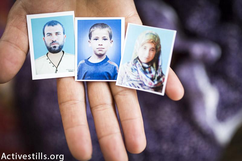 תמונות של ראדאד אחמד טנבורה (36), ושני ילדיו, אחמד (15) ואמה (13), מוחזקים בידיו אשתו אליז׳בת במה שנשאר מדירתם בית להיה, רצועת עזה, 19 למרץ, 2014. אליזבת נפצעה בהתקפה. (אן פאק / אקטיבסטילס)