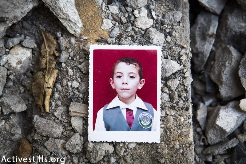 תמונה של עבדאללה אבדל האדי אל-מג׳דלאווי (13) מצולמת על חורבות ביתו, בו נהרג יחד עם שני אחדיו ושני בן דודים בהתקפה ישראלית, ג׳אבליה, רצועת עזה, 19 מרץ, 2015. (אן פאק / אקטיבסטילס)