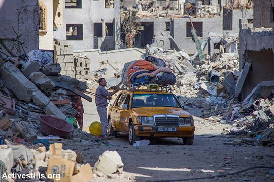 עזתי מחלץ חפצים אישיים משכונת בית חאנון המופצצת, עזה, 12 באוגוסט 2014. לפי נתוני האו״ם עד כה כ-16,800 בתים נהרסו כליל או ניזוקו קשה בעזה כתוצאה מההתקפות. (באסל יאזורי/אקטיבסטילס)