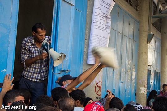 עזתים עומדים בתור לחלוקת אספקת המזון מאונר״א בזמן הפסקת האש, עזה, 17 באוגוסט 2014.  (אן פאק/אקטיבסטילס)