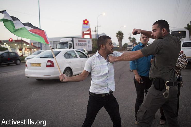חייל מג״ב מכוון ספרי פלפל לעבר אקטיביסט פלסטיני במהלך הפגנת סולדריות עם שובת הערב הפלסטיני מוחמד עלאן, ליד בית החולים ברזילי באשקלון, אוגוסט 16, 2015. (אורן זיו / אקטיבסטילס)