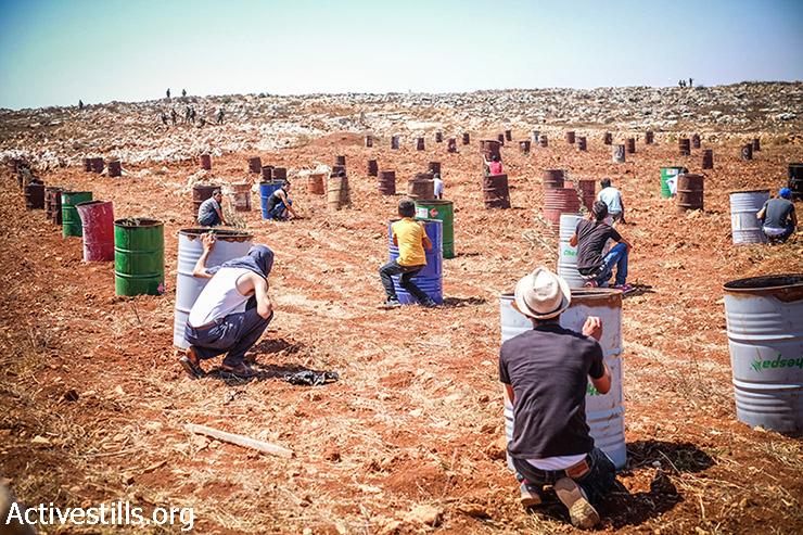 צעירים פלסטינים מגינים על עצמם מירי חיילים ישראליים במהלך התפרעות מתנחלים ליד הכפר קוסרא, הגדה המערבית, 22 אוגוסט, 2015. מתנחלים תקפו רועה פלסטיני ליד הכפר, והאירוע התפתח לתקרית בין הצבא והנערים שבו לעזרתו. שני צעירים פלסטינים נפצעו מירי הצבא. (יותם רונן / אקטיבסטילס)