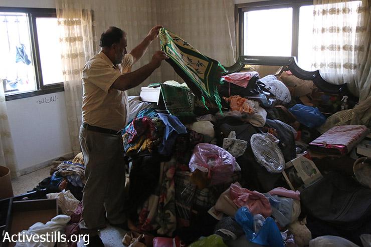 פלסטיני בוחן את הנזק שנגרם לביתו אחרי פשיטה לילית של הצבא בכפר סאלם ליד שכם, הגדה המערבית, 26 באןגןסט 2015. 31 פלסטינים נעצרו באותו הלילה בפשיטות ליליות דומות ברחבי הגדה. (אחמד אל באז / אקטיבסטילס)