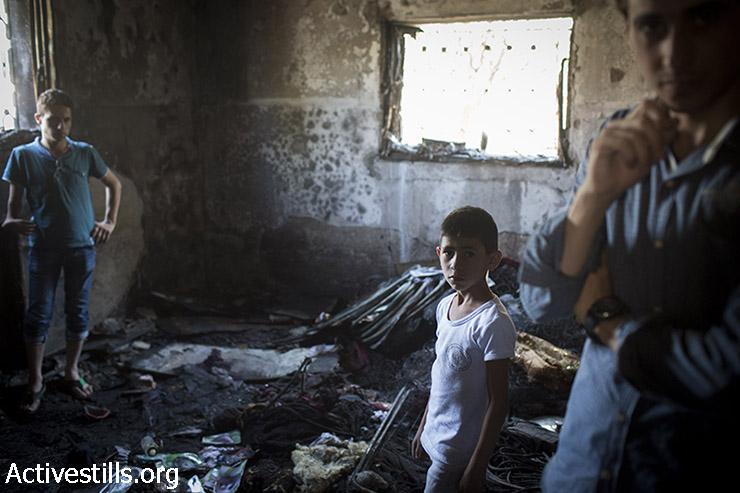 """פלסטינים מסתכלים על הנזק שנגרם לבית אשר הוצת על ידי מתנחלים יהודים בכפר דומא, דרומית לשכם, הגדה המערבית, 31 ביולי 2015. בעקבות ההצתה נשרף למוות הפעוט הפלסטיני בן 18 החודשים עלי דוואבשה, ואמו, אביו, ואחיו בן ה-4 אחמד נפצעו קשה.בית נוסף הוצת בכפר ועל קירות הבתים רוססו כתובות נאצה """"נקמה"""" ו""""יחי המלך המשיח"""". (אורן זיו/אקטיבסטילס)"""