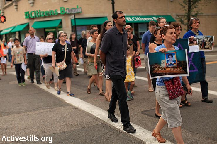 פעילים יהודים ותומכים צועדים לציון ולהנצחת ההתקפה הישראלית בעזה בקיץ 2014, שנה אחרי בברוקלין, ארה״ב, 26 ביולי 2014. הצועדים נשאו תמונות שצולמו ע״י צלמי אקטיבסטילס בעזה במהלך התקפה ולאחריה. (טס שפלן/אקטיבסטילס)