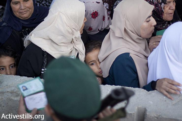 פלסטיניות חוצות את מחסום 300 שבין בית לחם וירושלים בדרכם לתפילה במסגד אל-אקצא בירושלים, ביום שישי השלישי של חודש הרמדאן, 3 ביולי, 2015. (מוסטפה באדר/אקטיבסטילס)